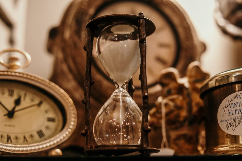 an hourglass and other clocks