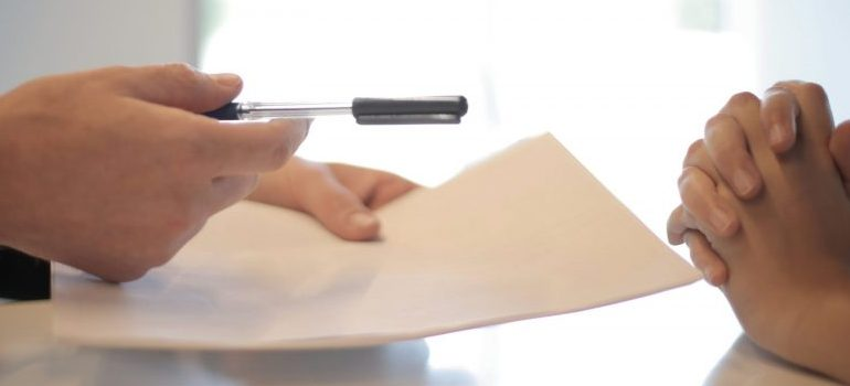 person offering a pen to another