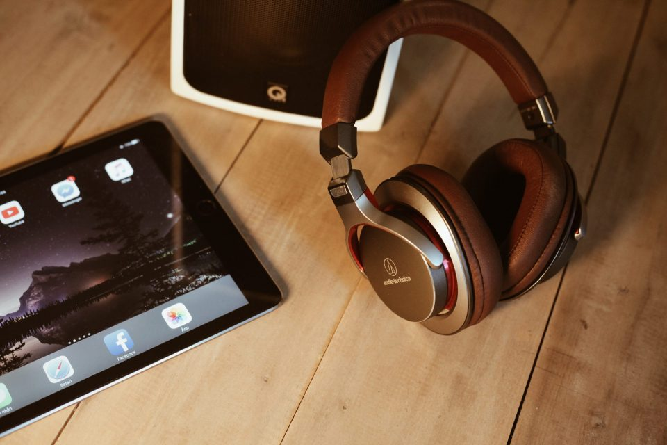 headphones, a tablet, and a small speaker on a desk