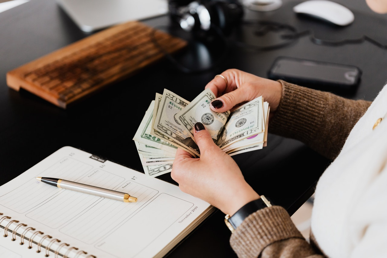a woman counting money at her work desk