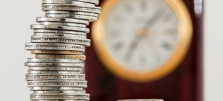 a stack of silver coins with a clock on the wall behind it