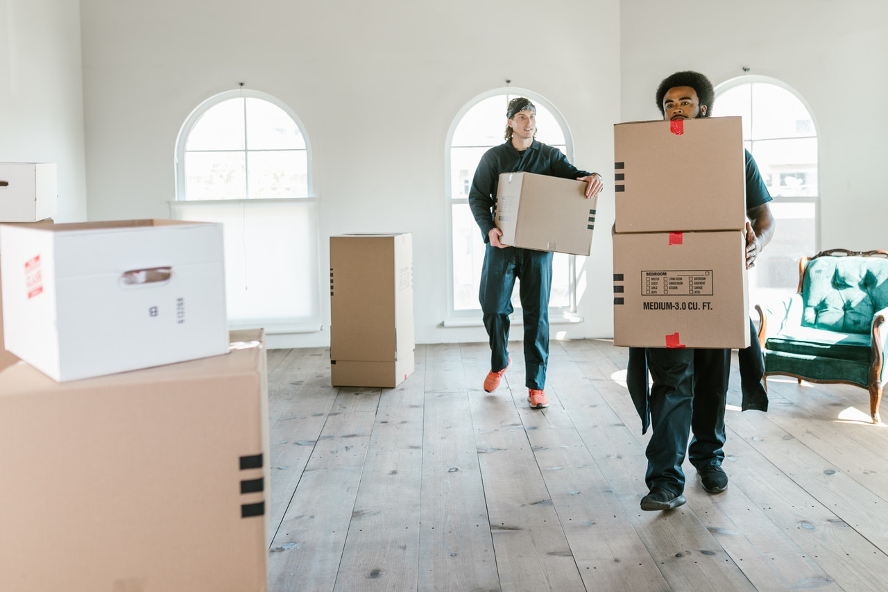 two movers carrying cardboard boxes out of the house