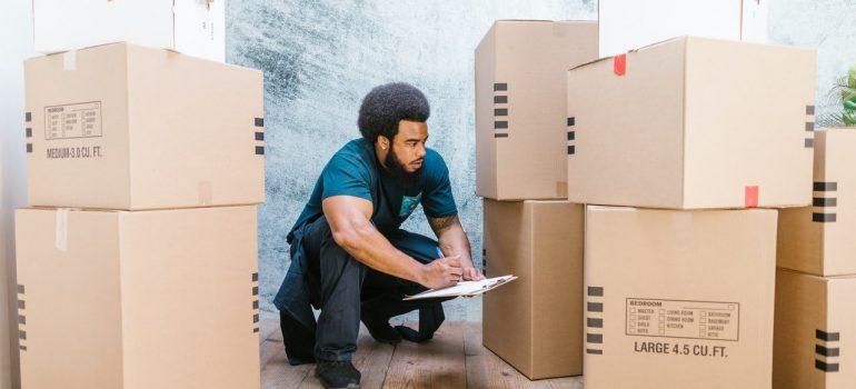 a man crouching between cardboard boxes as he writes down something